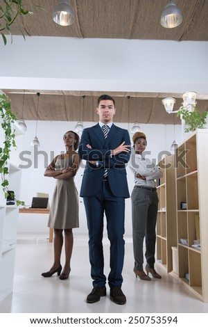 Serious business team standing together at office full length - stock photo