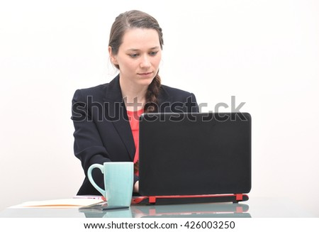 Serious business woman looking at computer - stock photo