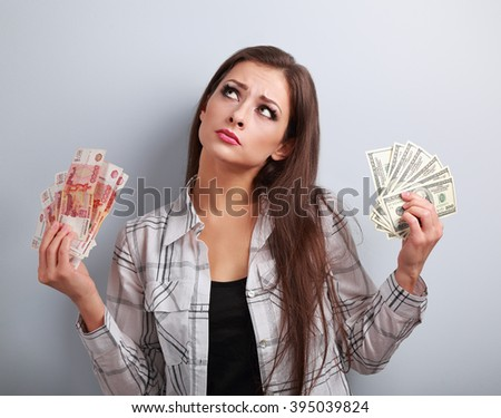 Serious business woman thinking that currency to choose, dollars or rubles, holding money in different hands