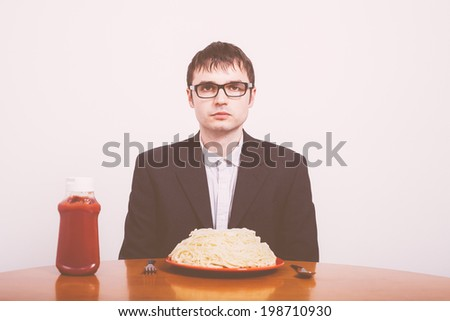 Serious businessman and pasta with ketchup on the table.