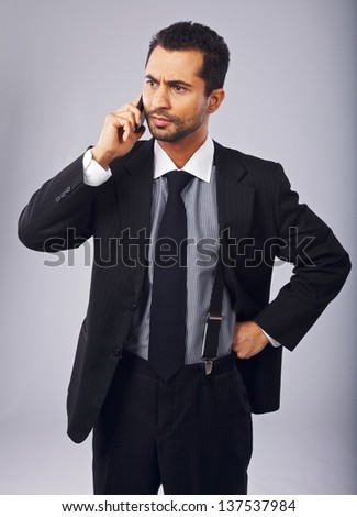 Serious businessman annoyed by a phone call - stock photo