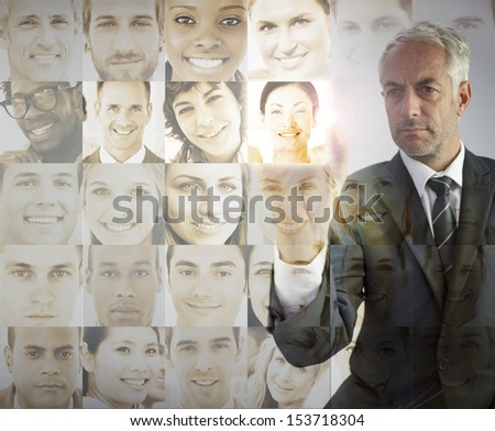 Serious businessman choosing future employees on digital interfaces - stock photo