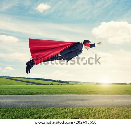 serious businessman dressed as a superhero in red mask and cloak flying at outdoor over beautiful landscape background - stock photo