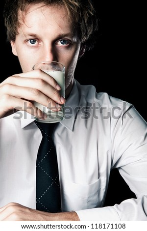 Serious businessman drinking glass of milk rich in calcium, desaturated with black background - stock photo