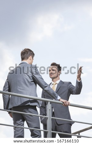 Serious businessman gesturing while looking at coworker against sky