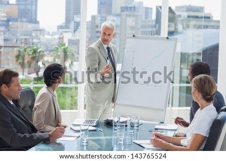Serious businessman giving a presentation with colleagues looking at him - stock photo