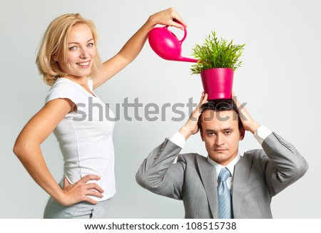 Serious businessman holding a plant on his head, cheerful young woman watering it