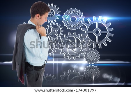 Serious businessman holding his jacket against cogs and wheels graphic