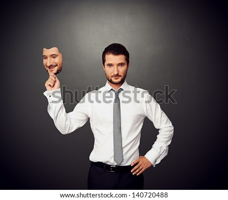 serious businessman holding mask with good mood - stock photo