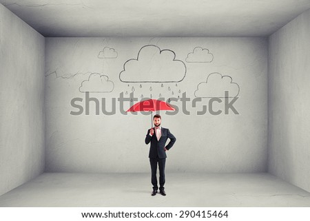serious businessman holding red umbrella under graphic clouds with rain in empty grey concrete room