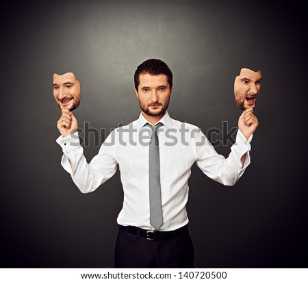 serious businessman holding two masks with different mood - stock photo