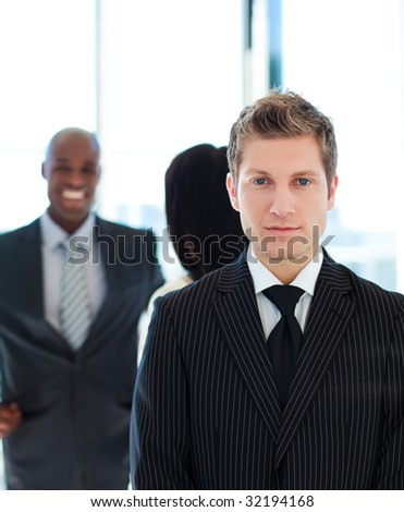 Serious businessman in front of his team in office