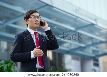 Serious businessman in glasses talking on the phone