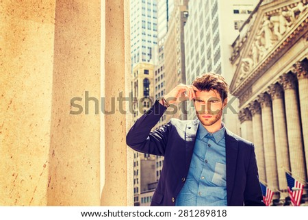 Serious businessman in New York. Dressing in blue suit, arm against column, hand touching forehead, a young guy with beard, looking down, frowned, sad, expressed troubling feelings. Instagram effect. - stock photo