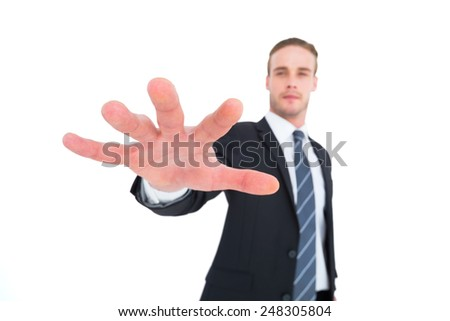 Serious businessman in suit gesturing on white background - stock photo