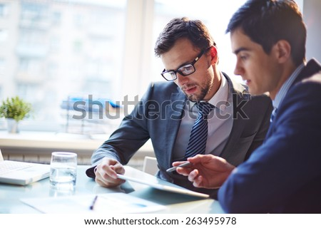 Serious businessman listening to his colleague explanations at meeting - stock photo