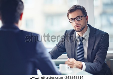 Serious businessman looking at camera at workplace with his colleague near by - stock photo