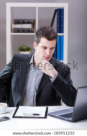Serious businessman looking at computer monitor in his office