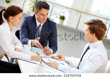 Serious businessman looking at his employee while commenting his report  - stock photo