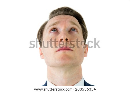 Serious businessman looking at top on white background