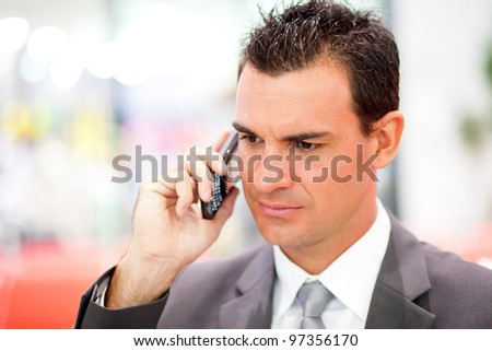 serious businessman on cell phone - stock photo