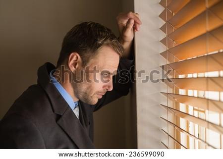 Serious businessman peeking through blinds in office - stock photo
