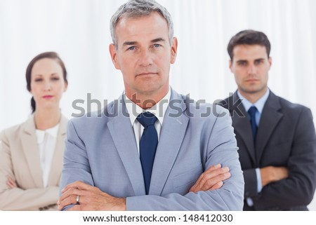 Serious businessman posing with his work team in bright office - stock photo