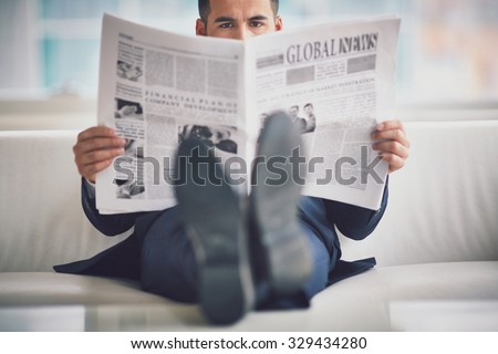 Serious businessman reading newspaper in office