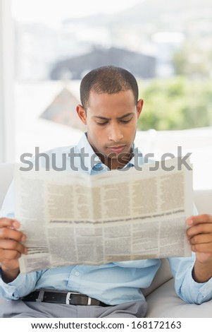 Serious businessman reading newspaper on the couch in the office