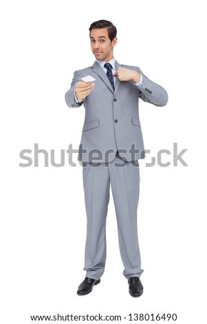 Serious businessman showing his business card on white background - stock photo