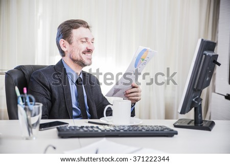serious businessman sitting at his desk and  read business documents and smiles - stock photo