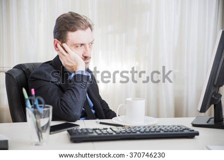 serious businessman sitting at his desk and  read business news - stock photo