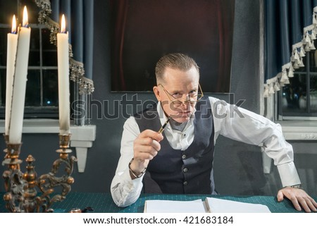 Serious businessman sitting at the table with pens in hand