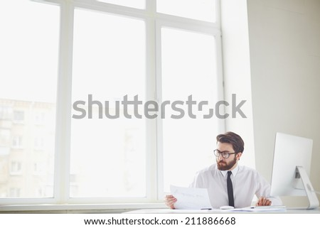 Serious businessman sitting in office and working with papers - stock photo
