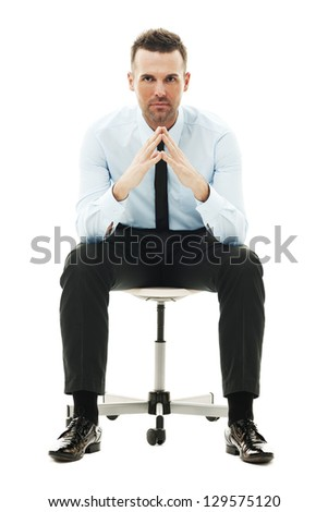 Serious businessman sitting on chair - stock photo