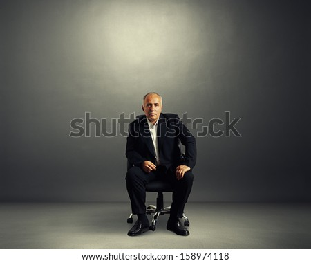 serious businessman sitting on the office chair and looking at camera - stock photo