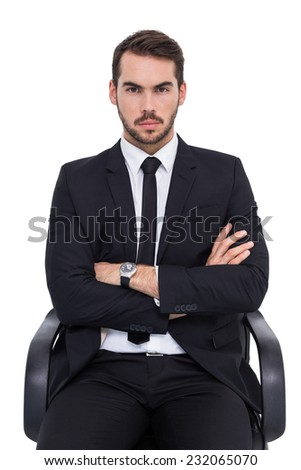 Serious businessman sitting with arms crossed on white background