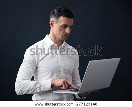 Serious businessman standing and using laptop over black background - stock photo