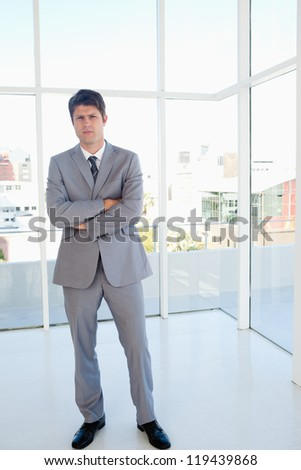 Serious businessman standing in a bright space - stock photo