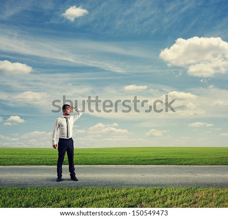 serious businessman standing on road and looking forward