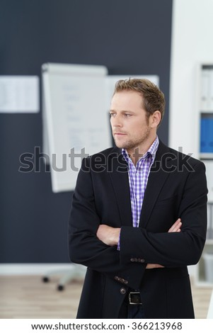 Serious businessman standing waiting with crossed arms and an impatient expression , upper body in the office - stock photo