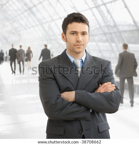 Serious businessman standing with arms crossed in office lobby, looking at camera. - stock photo
