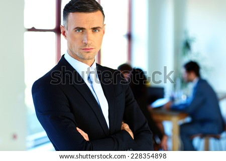 Serious businessman standing with arms folded in front of colleagues - stock photo