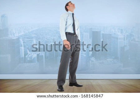 Serious businessman standing with hand in pocket against city scene in a room