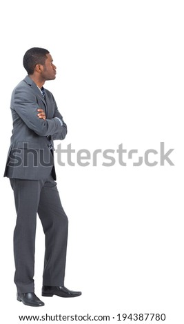 Serious businessman standing with his arms folded on white background - stock photo