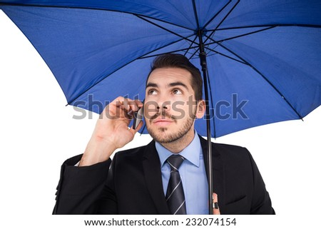 Serious businessman under umbrella phoning on white background - stock photo