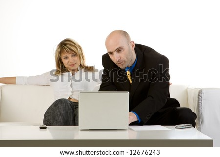 Serious businessman using a laptop computer while dealing with a young female customer.  Both are sitting on a white couch.  Isolated on a white background. - stock photo
