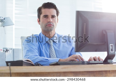 Serious businessman using computer in his office