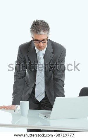 Serious businessman using laptop computer, standing behind office desk, looking down. Isolated on white.