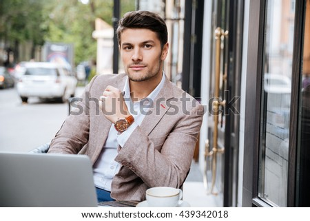 Serious businessman using modern laptop and thinking about something in coffee shop